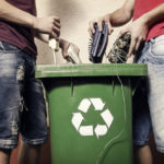 Office workers placing old electronics into a recycling bin to show how easy Electronic Waste Recycling can be for your business, school, non-profit, or government agency.